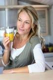 Portrait of blond woman drinking orange juice. Portrait of blond woman in kitchen drinking orange juice Royalty Free Stock Image