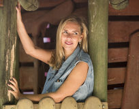 Portrait of blond woman in front of a cabin Royalty Free Stock Photography