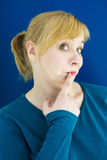Portrait of blond woman holding finger to her mouth Stock Photos
