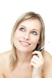 Portrait of a blond woman holding a lipstick Royalty Free Stock Images