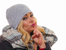 Portrait of a blond woman. Image of a blond woman dressed for winter with finger up to her lips Royalty Free Stock Photography