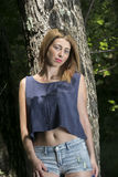 Portrait of a blond woman leaning on a tree. Portrait of a blond woman with blue eyes, pretty face with short straight hair, wear crop top and shorts leaning on stock photo