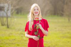 Portrait of blond woman. In red maxi dress outdoor Royalty Free Stock Image