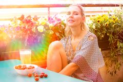 Portrait of a blond woman sitting on balcony Royalty Free Stock Photography
