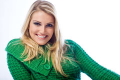 Portrait of a blond woman smiling at camera. Portrait of a leaning blond woman smiling at camera wearing a green knitwear sweater on a white background Royalty Free Stock Photo