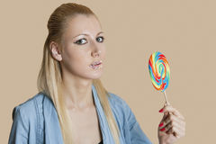 Portrait of a blond woman with sprinkled lips holding lollipop over colored background Royalty Free Stock Photos