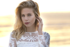 A portrait of a blond woman standing with a lace dress during sunrise in front of ocean. Stock Photos