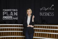 Portrait of a blond woman thinking about money-making. Business concept. Portrait of a blond woman in black suit thinking about money-making. Business concept Stock Photo