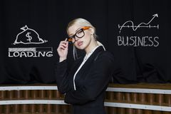 Portrait of a blond woman thinking about money-making. Business concept. Portrait of a blond woman in black suit thinking about money-making. Business concept Royalty Free Stock Photo