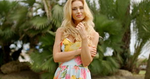 Portrait of Blond Woman in Tropical Location. Portrait of Blond Woman Wearing Floral Print Sun Dress Standing with Arms Across Body and Looking at Camera stock video footage