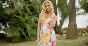 Portrait of Blond Woman in Tropical Location. Portrait of Blond Woman Wearing Floral Print Sun Dress Standing with Arms Across Body and Looking at Camera stock video