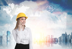 Portrait of blond woman wearing hard hat and talking on smartphone. Royalty Free Stock Image