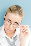 Portrait of a blond young business woman looking over square spectacles Stock Photography