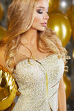 Portrait of blond young woman between golden balloons and ribbon Royalty Free Stock Photography