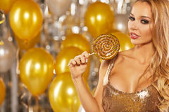 Portrait of blond young woman between golden balloons and ribbon Stock Images