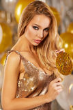 Portrait of blond young woman between golden balloons and ribbon Royalty Free Stock Image