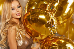 Portrait of blond young woman between golden balloons and ribbon Stock Image