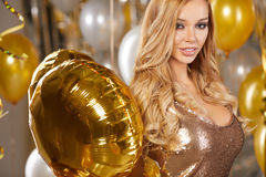 Portrait of blond young woman between golden balloons and ribbon Royalty Free Stock Photos