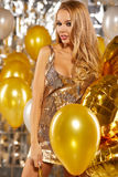 Portrait of blond young woman between golden balloons and ribbon Royalty Free Stock Photo