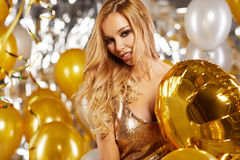 Portrait of blond young woman between golden balloons and ribbon Stock Photography
