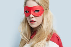 Portrait of a blond young woman wearing red eye mask against light blue background Stock Image