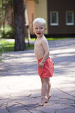 Portrait of blonde baby boy in red shorts. Standing on tiptoe. Portrait of blonde baby boy in red shorts walking in summer park Stock Photo