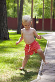 Portrait of blonde baby boy in red shorts. Walking in summer park Royalty Free Stock Photography