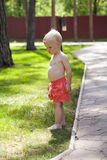 Portrait of blonde baby boy in red shorts. Walking in summer park Stock Photo