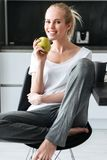 Portrait of blonde lady sitting and looking camera in kitchen. Portrait of blonde beautiful lady sitting with apple and looking camera in kitchen Royalty Free Stock Images
