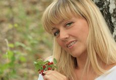 Portrait of the blonde with berries royalty free stock images