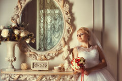 Portrait of blonde bride near the mirror. Beautiful bride with a bouquet of standing near mirror in luxury interior Stock Photography