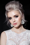 Portrait of blonde bride wearing lace dress, earrings with diamonds posing at camera in dark studio. Gorgeous woman with stylish h Stock Photography