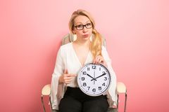 Businesswoman boss with clocks. Portrait of blonde businesswoman boss in eyeglasses sitting in chair isolated on pink background holding clocks and pointing at Stock Image