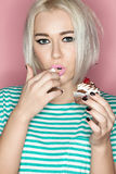Portrait of a blonde with cake. Portrait of a beautiful blonde eating cake with his hands and looking into the camera on pink background Royalty Free Stock Photography
