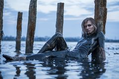 Portrait of Blonde Caucasian Girl Lays Smeared in a Healthy Black Mud in old Firth with Wooden Posts for Salt Production. Portrait of Blonde Caucasian Girl Lays royalty free stock photography