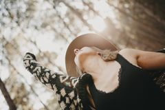 Blonde woman with a hat looking up and raising arm up in the countryside. stock image