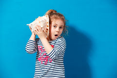 Portrait of blonde child girl listen a seashell at the blue wall. Summer vacation concept Stock Images