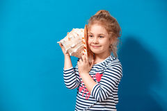 Portrait of blonde child girl listen a seashell at the blue wall. Summer vacation concept Stock Photos