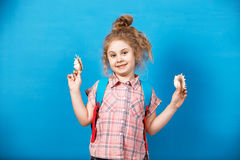 Portrait of blonde child girl listen a seashell at the blue wall. Summer vacation concept Royalty Free Stock Photos