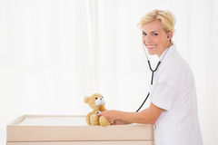 Portrait of a blonde doctor with stethoscope and teddy bear Royalty Free Stock Photography