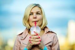 Portrait of blonde drinking milkshake Stock Image