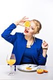 Portrait of blonde elegant woman holding cut orange near eye Stock Image