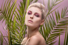 Portrait of blonde girl with artistic makeup. Closeup beauty portrait of attractive blonde woman with glamour artistic makeup stock images