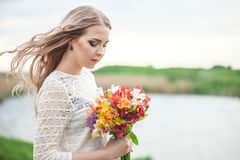 Portrait of a blond girl with a bouquet of flowers on a lake background close-up stock photos