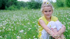 Portrait. Blonde girl, child, sits in the grass, among the daisies, in the meadow. Her hair is decorated with daisies stock video