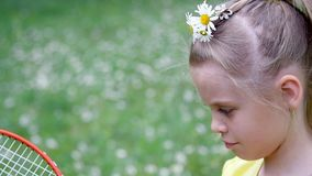 Portrait. Blonde girl, child, sits in the grass, among the daisies, in the meadow. Her hair is decorated with daisies stock video footage
