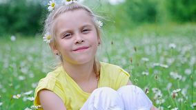 Portrait. Blonde girl, child, sits in the grass, among the daisies, in the meadow. Her hair is decorated with daisies stock footage