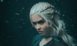 Portrait of a blonde girl close up. Background dark with flying snow, ash. White hair with creative braiding. Emotions. Of anger, and madness. The gothic queen royalty free stock photography