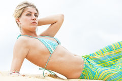 Portrait of the blonde girl lying on the sand Royalty Free Stock Photos