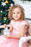 Portrait of a blonde girl in a pink dress against the backdrop of a Christmas tree with a white candlestick in the hands. Portrait of girl in a pink dress Stock Photos